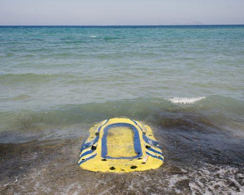 Tourists vs. Refugees; Zurückgelassenes Schlauchboot von Flüchtlingen am Strand, August 2015, Kos, Insel Kos, Griechenland, Europa, © Joerg Brueggemann/OSTKREUZ